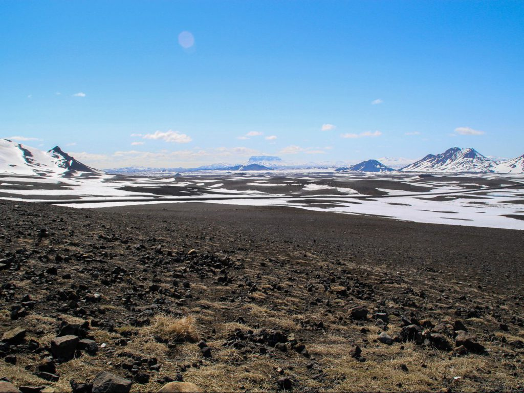 Lava field and mountain peaks on Iceland covered in snow