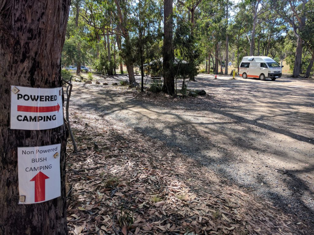 Signpost to powered and non powered campsites and campervan on campsite Tasmania