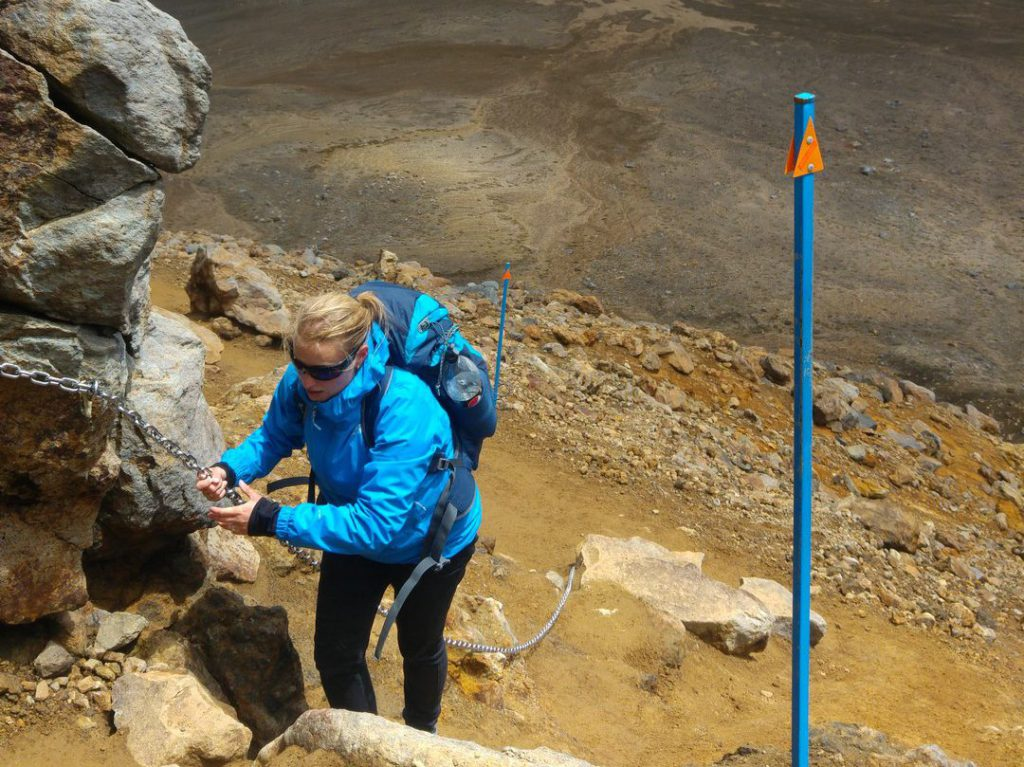 Hiker climbs up via steel chain near South Crater Tongariro Alpine Crossing New Zealand