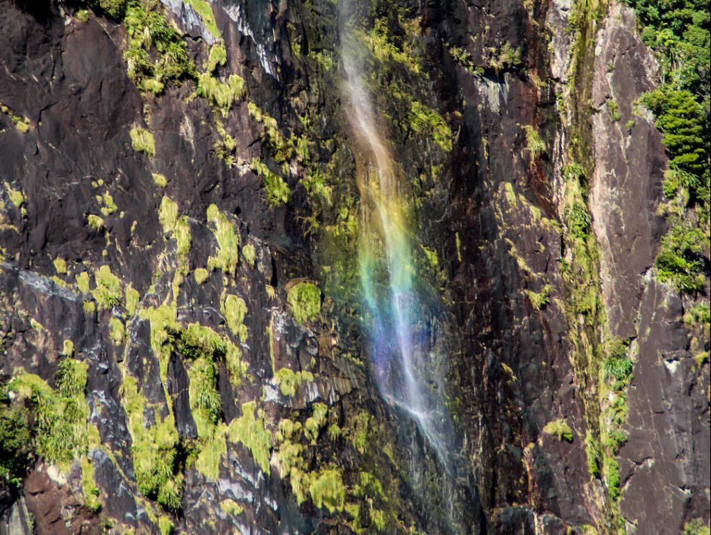 Colors of rainbow are visible in waterfall Milford Sound New Zealand