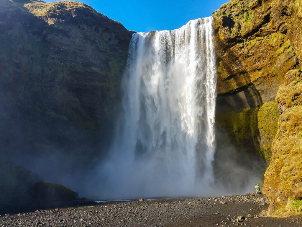 Visitors standing next to Skógafoss waterfall Iceland
