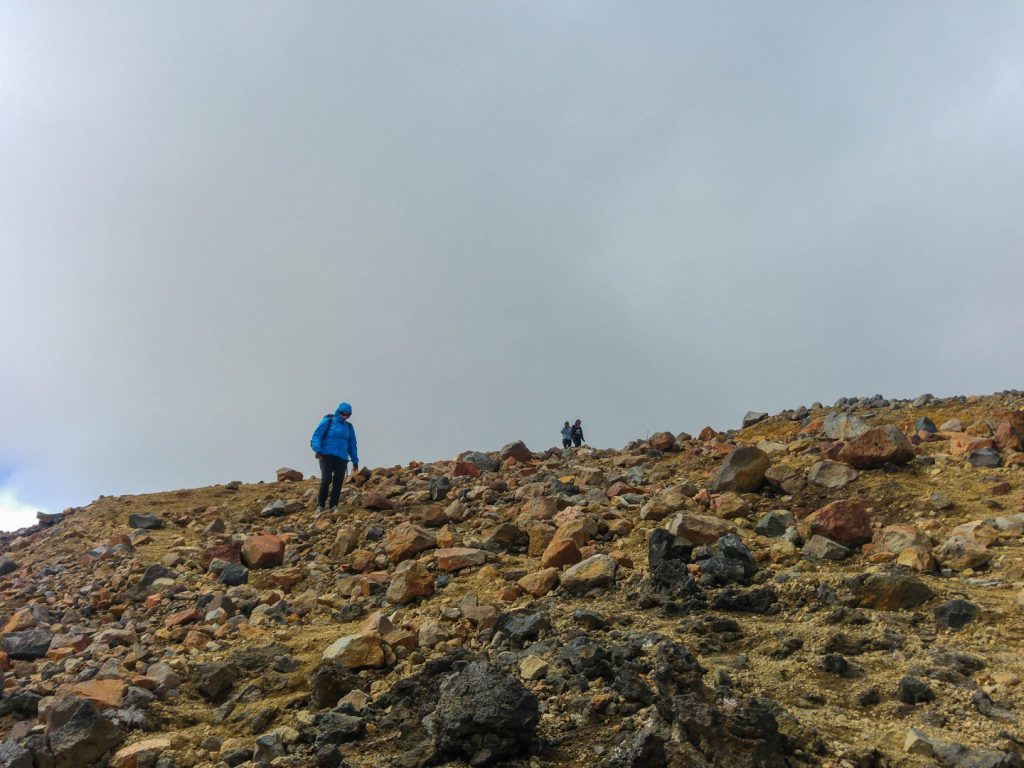 Hiker descends on path full of stones Tongariro Alpine Crossing New Zealand