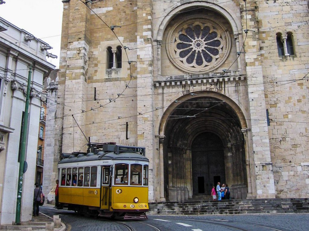 Yellow tram passes Lisbon cathedral