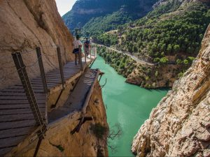 Old and new hiking trail hanging above emerald green river El Caminito del Rey Spain