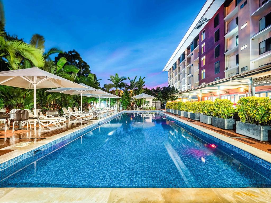 Swimming pool in garden with sunbeds at Novotel Darwin Airport hotel
