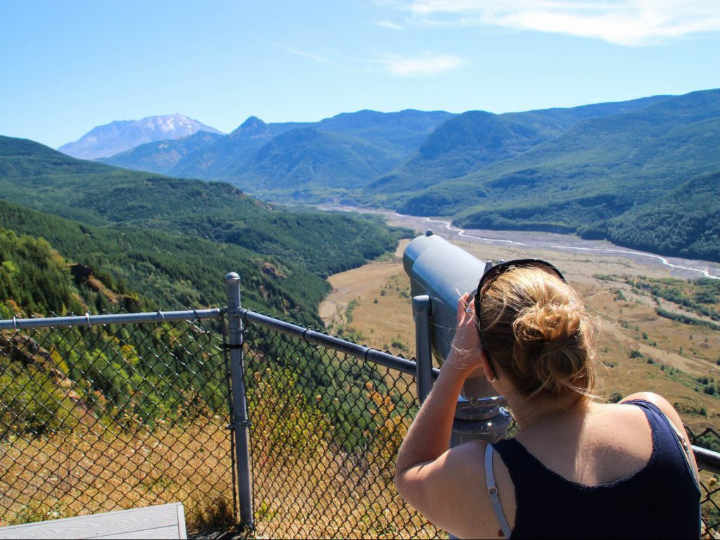 visitor enjoys view of volcano Mount St Helens and Toutle River with binoculars at Forest Learning Center
