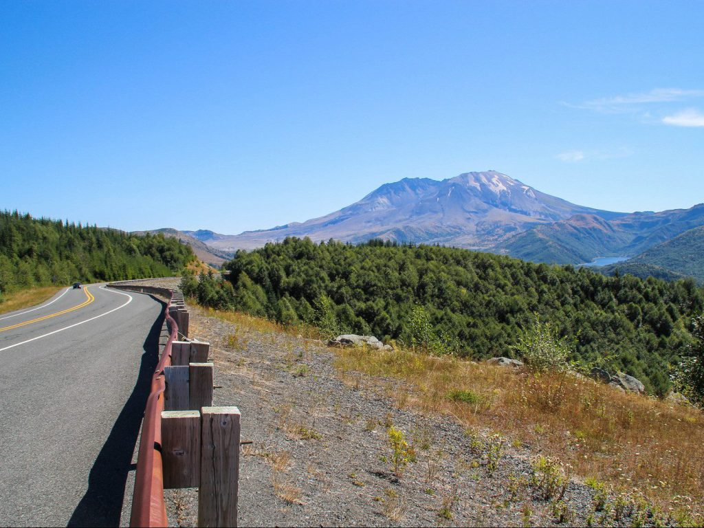 road with guardrail and view of volcano Mount St Helens and Castle Lake