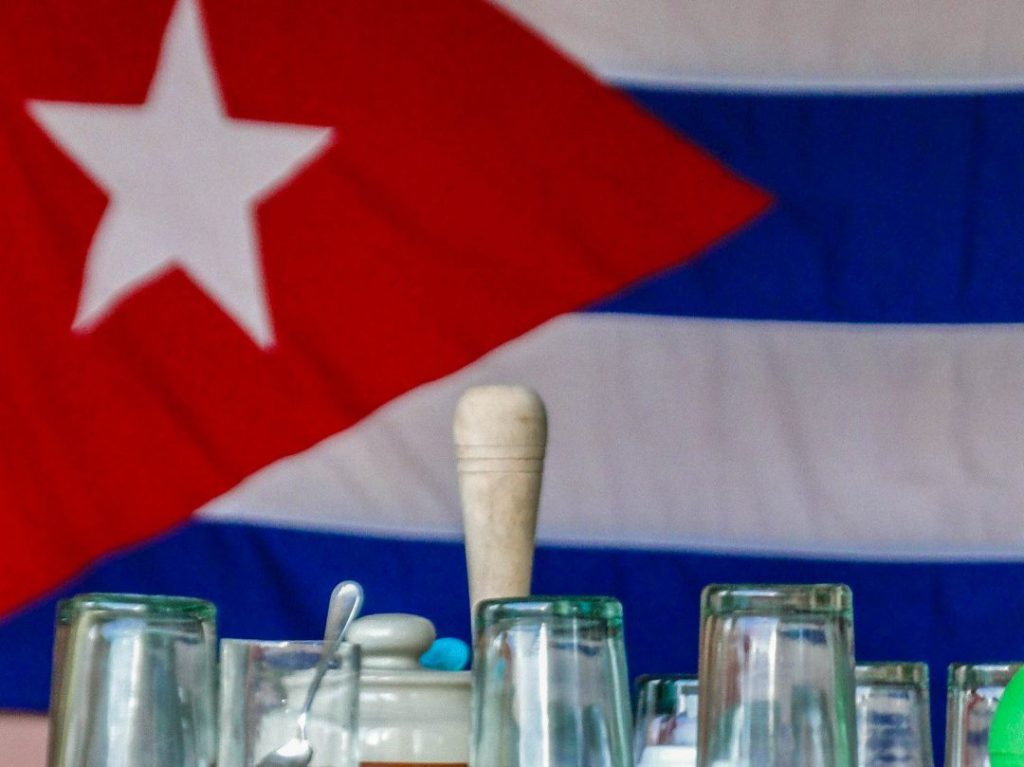 glasses in front of Cuban flag
