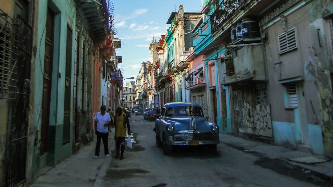 old-timer in street colored colonial buildings Havana Cuba