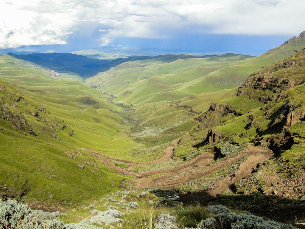 view of jeep in landscape with hairpin bends at Sani pass